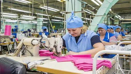 швея на фабрике строчит на швейной машинке