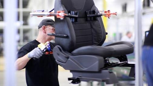 мужчина на фабрике по производству автомобильных сидений работает возле конвеера