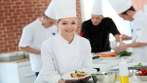 Девушка повар в колпаке на кухне ресторана с блюдом в руке