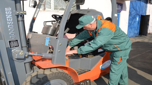 Мужчина автоэлектрик ремонтирует погрузчик