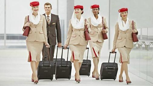 стардессы авикомпании Emirates идут с чемоданами в аєропорту