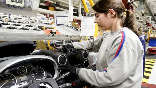девушка работает на конвеера на автомобильном заводе